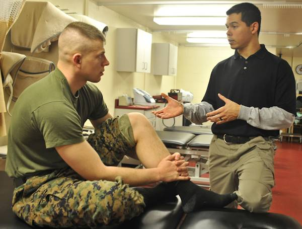 During a one-on-one session at Ramer Hall on Jan. 17, 2013, Edward J. Sedory, certified athletic trainer, The Basic School, explains to a Marine why he has troubles performing simple tasks with his leg. Sedory wanted to be a athletic trainer since his freshman year in high school. (U.S. Marine Corps photo by Lance Cpl. Antwaun L. Jefferson)