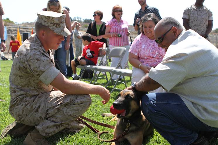 Sgt. Jonathan Overland, a dog handler with 1st Law Enforcement Battalion, hands Dino off to the Diaz family during a retirement and adoption ceremony at a kennel aboard Marine Corps Base Camp Pendleton, Calif., June 7, 2014. The Diaz family waited 3 years since the passing of their son, Staff Sgt. Christopher Diaz, a dog handler with III Marine Expeditionary Force, to adopt Dino, their son's military working dog. (U.S. Marine Corps photo by Lance Cpl. Angel Serna)