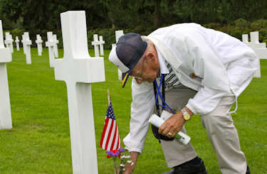 Veteran Bill Kamsler places flowers at a fellow.