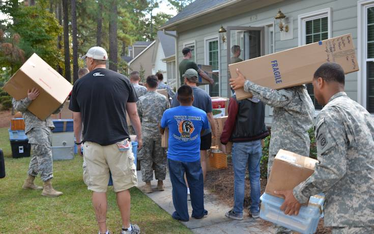 Volunteers from the Fayetteville, N.C., community form a line, holding boxes of household goods they unloaded from a self-storage container to help Chief Warrant Officer 5 Charles Petrie, an Army officer who has given almost 30 years to his country and is now terminally ill, and his family move into their new home. Petrie was diagnosed with sarcoma in his sinus – one of the rarest forms of cancer and in the rarest place, according to his wife, Terri. Despite multiple, large radiation treatments that shrank the tumor, the cancer is growing again. After being contacted by someone close to the family, U.S Army W.T.F! Moments took action by posting a message to their Facebook audience of more than 328,000 people. Approximately 100 soldiers, retirees, and civilians showed up to help a fellow soldier in need, Sept. 27, 2013 at a home in Fayetteville, N.C. (U.S. Army photo by Sgt. Amie J. McMillan, 10th Press Camp Headquarters)