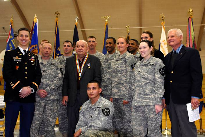 "Silver Star recipient, William V. Wuorinen (center left), is surrounded by soldiers from 4th Battalion, 9th Infantry Regiment, 4th Stryker Brigade Combat Team, 2nd Infantry Division along with the unit's rear detachment commander and former platoon leader, Capt. Michael Centola (left), and retired Lt. Col. Gil Blue (right), after an award ceremony held at Naselle-Grays River Valley School, Naselle, Wash., Jan. 30,2013. The Silver Star medal was presented to Wuorinen for his ""gallantry in action"" between March 16, 1953, and March 17, 1953, while serving as an infantryman. Photo by Army Spc. Reese Von Rogatsz"