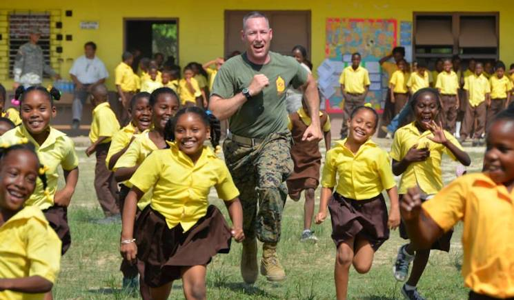 U.S. Marine Corps Gunnery Sgt. Keith Day challenges Hattieville Government School students to a race during a physical fitness lesson he led on May 13, 2014. Day is deployed in support of the New Horizons training exercise in Belize. (U.S. Air Force photo by Master Sgt. Kelly Ogden)