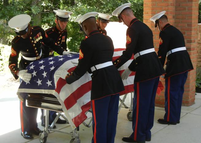 Marines from Quantico's Ceremonial Platoon smooth the American flag over the casket at a funeral at Quantico National Cemetery September 13, 2012. Photo by USMC Lance Cpl. Tabitha Bartley