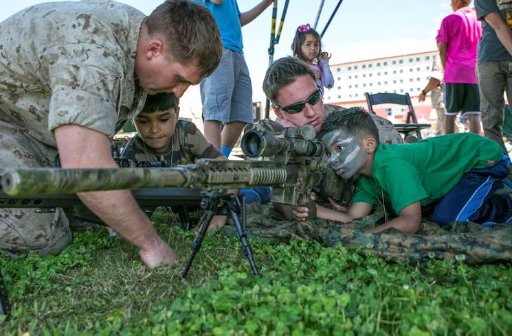 "Ayaan Vicente, 6, looks through the scope of an M110 semi-automatic sniper system as Cpl. Justin B. Federhofer supervises on April 11, 2014 at Camp Schwab during the 3rd Reconnaissance Battalion's annual ""Do What Daddy Does"" day. The children simulated using equipment and performing duties as their fathers would. Federhofer is a reconnaissance man with 3rd Recon Bn., 3rd Marine Division, III Marine Expeditionary Force. (U.S. Marine Corps photo by Cpl. Jose Lujano)"