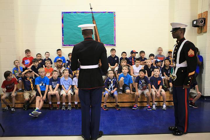 Lance Cpl. Joshua Pineset, a Marine Forces Reserve administrative specialist and color guard member, demonstrates color guard rifle manual for Cub Scout Pack 454 at Belle Chasse Academy here, Sept. 12, 2013. Marines from the MARFORRES color guard attended the pack's first meeting of the school year to demonstrate and teach proper color guard skills and procedures. (U.S. Marine Corps photo by Lance Cpl. Tiffany Edwards)