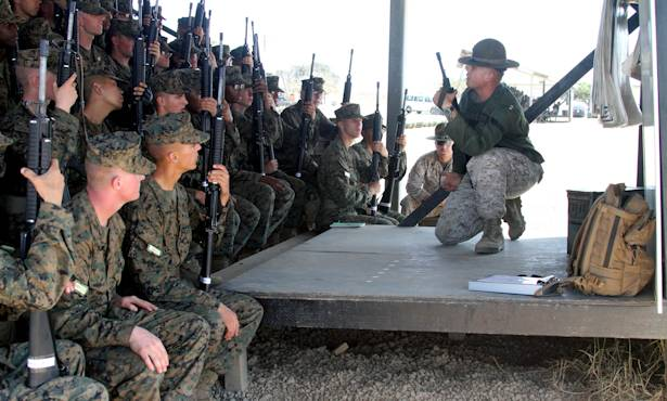 Sgt. Ryan Salinas, primary marksmanship instructor, Weapons Company, Weapons and Field Training Battalion, demonstrates the kneeling position to the recruits of Company F, 2nd Recruit Training Battalion, Oct. 2, 2012 at Edson Range aboard Marine Corps Base Camp Pendleton. Grass Week is dedicated to teaching the fundamentals of marksmanship and allows recruits to become comfortable with the weapon. Photo by USMC Lance Cpl. Bridget Keane