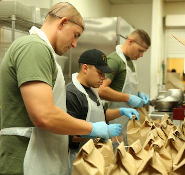 Staff Sgt. Abel Olmstead, company gunnery sergeant, 3rd Battalion, 4th Marines, 7th Marine Regiment, packs lunches during a volunteer event at the St. Vincent de Paul Village, May 25, 2014. Packing lunches was one of several tasks the group carried out in the kitchen, as well as serving food and chopping fruit. (U.S. Marine Corps photo by Lance Cpl. Paul Martinez)