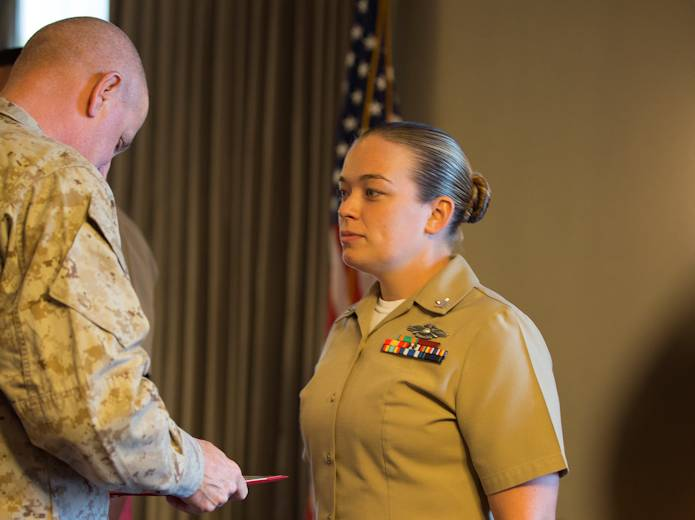 Petty Officer 2nd Class Emily Riley, a corpsman with Marine Heavy Helicopter Squadron 466 and a Dallas native, receives the 3rd Marine Aircraft Wing's Junior Sailor of the Quarter Award from Maj. Gen. Steven Busby, 3rd MAW commanding general, aboard Marine Corps Air Station Miramar, CA on Aug. 16, 2013. Riley stood out from other sailors in her command by excelling at daily tasks, taking on collateral duties and also singing the national anthem at various ceremonies both on and off the air station. (U.S. Marine Corps photo by Cpl. Kevin Crist)
