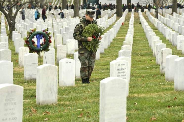 United States Naval Sea Cadet Corps' Stephen Christopher Clark lays a wreath at the grave of his grandfather, Navy Cmdr. Stephen P. Ragan, in Arlington National Cemetery's Section 60 at the beginning of Wreaths Across America's laying of 143,000 remembrance wreaths on December 14, 2013. (Joint Base Myer-Henderson Hall Pentagram photo by Jim Dresbach)
