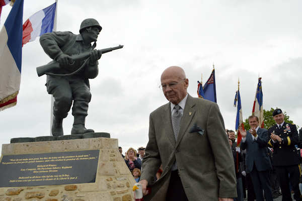 Former Homeland Security Director Tom Ridge and Maj. Gen. Jim McConville, commander of the 101st Airborne Division (Air Assault), watch as Herb Suerth, a veteran of Company E, 2nd Battalion, 506th Parachute Infantry Regiment, walks past the Maj. Richard Winters Leadership monument, dedicated June 6, 2012, near Utah Beach in Normandy, France. Photo by Warrant Officer Patrick Brion, Belgian Armed Forces