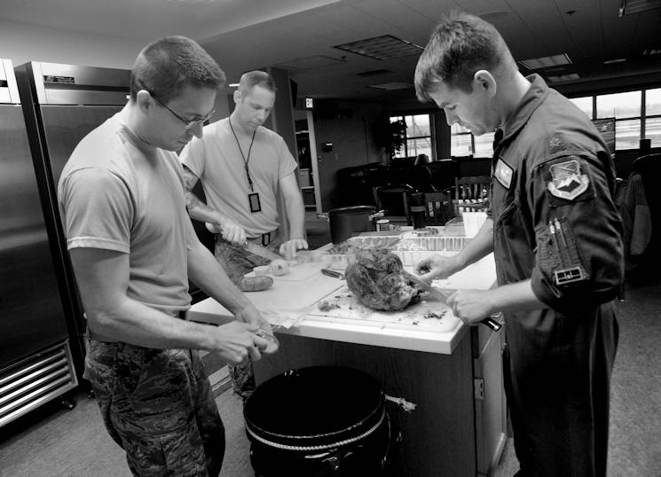 Oregon Air National Guard Maj. Bradley Young, a pilot assigned to the 123rd Fighter Squadron, 142nd Fighter Wing, Portland Air National Guard Base, Ore., cuts a Thanksgiving Turkey at the Alert Facility, as Staff Sgt. Matthew Shelburne, left, and Tech. Sgt. Kyle Adair, center, prepare potatoes for dinner on Nov. 27, 2014. (U.S. Air National Guard photo by Tech. Sgt. John Hughel, 142nd Fighter Wing Public Affair)