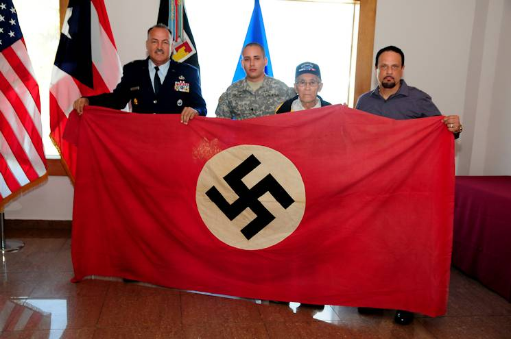The Puerto Rico National Guard receives a captured Nazi flag from retired Col. Arnaldo Claudio, Interagency program director of the joint staff in Washington D.C., in a ceremony held at the PRNG-Joint Forces Headquarters in San Juan on December 19, 2013. From left to right, the Adjutant General of Puerto Rico, AF Brig. Gen. Juan J. Medina Lamela, Spec. Wesley Ortiz, member of A Company 1 Battalion 65th Infantry Reg., Julio Burgos Santiago, veteran of the 65th Infantry Regiment and retired Col. Arnaldo Claudio. More than 65,000 Puerto Ricans participated in all Armed Forces branches during World War II. (Courtesy Photo)