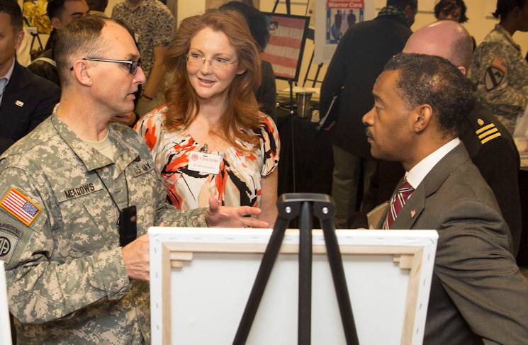 From left, Staff Sgt. Jonathan Meadows and wife Melissa speak with Jonathan Woodson, assistant secretary of defense for Health Affairs, during an exhibition at the rehabilitation expo Nov. 20, 2014, in Arlington, Va., within the Pentagon's corridors. (Joint Base Myer-Henderson Hall PAO photo by Damien Salas)