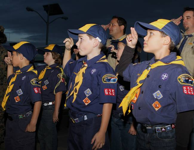 Cub Scouts and den leadership with Wolf Scout Den 3, Pack 625, Poway, Calif., salute the American flag during evening colors ceremony aboard Marine Corps Air Station Miramar, Calif., Nov. 15, 2012. When saluting, Cub Scouts and Boy Scouts of all ages stand still and raise their first two fingers to the bill of their hats or edge of the forehead as a sign of respect. Photo by USMC Lance Cpl. Christopher Johns