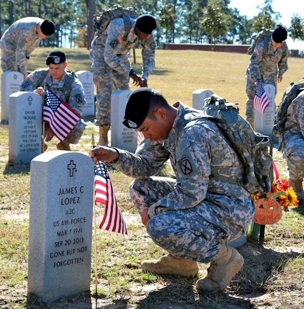 Spc. Matthew Corfman, Headquarters Company, 94th BSB, 4th BCT, 10th Mtn. Div. says a prayer as he places a flag at the headstone of a veteran ... while over 100 of his fellow soldiers were placing flags on other veterans' headstones at the CENLA Veterans Cemetery on November 7, 2014 in association of Veterans Day on November 11th. (Photo by U.S. Army Sgt. David Edge, PAO NCO)