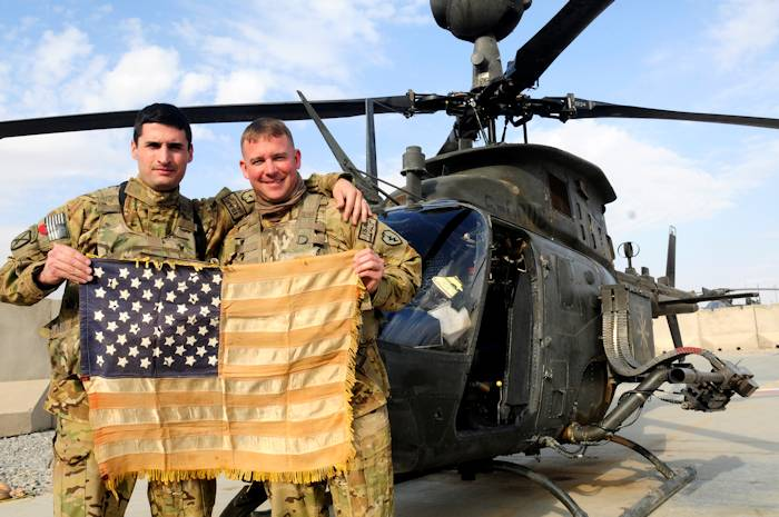 Capt. Matt Louer, Headquarters and Headquarters Company, 25th Combat Aviation Brigade, and Chief Warrant Officer 3 Jason Call, 2nd Squadron, 6th Cavalry Regiment, 25th CAB, pause for a photo with the Hoe Battle Flag before flying a mission with the Hoe Battle Flag on Thanksgiving Day (November 22, 2012) on Kandahar Airfield, Afghanistan. Louer has the honor to fly the Hoe Battle Flag on Thanksgiving for his last flight in the Army.
