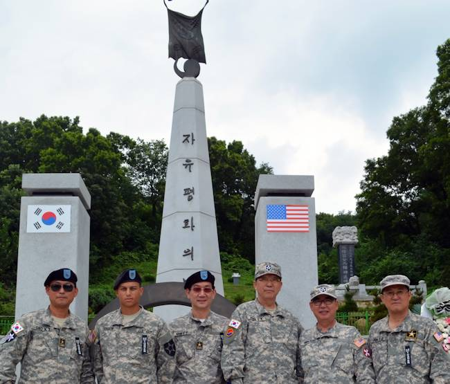Pvt. Joshua Gordon, from Ann Arbor, Mich., assigned to the Company E, 3rd General Support Aviation Battalion, 2nd Combat Aviation Brigade poses for a picture with members of the Korean Augmentation to the United States Army Veterans Association (Daejeon city, Chungcheon Province, Seijong city Chapter) in front of the Splendor of Peace and Freedom monument after the Gaemi Hill Memorial Ceremony July 11, 2013 located near Jochiwon, South Korea. (U.S. Army photo by Staff Sgt. Aaron P. Duncan, 2nd CAB PAO)