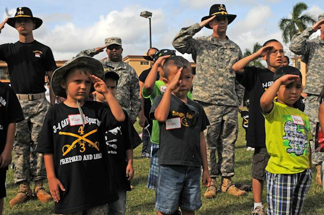 Soldiers of 3rd Squadron, 4th Cavalry Regiment, 3rd Brigade Combat Team, 25th Infantry Division and junior Raiders salute the colors during the playing of the national anthem at the Junior Spur Ride, here, March 21, 2013. (Photo by Staff Sgt. Cashmere C. Jefferson, 3rd Brigade Combat Team Public Affairs)