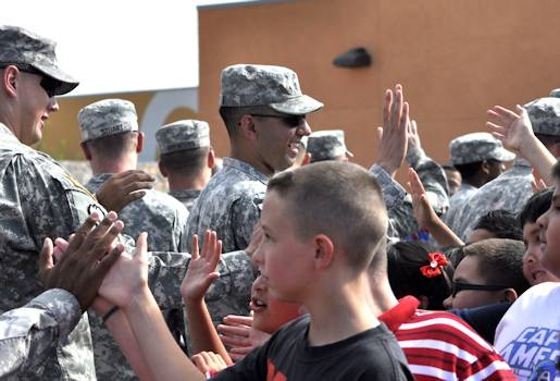 Sgt. Muhammad Sheikh, president of Better Opportunities for Single Soldiers, and fellow soldiers greet children at the September 11th Commemorative Program at the Chester Jordan Elementary School on Sept. 11, 2012 in El Paso, Texas. More than 50 soldiers with the BOSS program attended the ceremony to honor those who sacrifice themselves to protect the people of America both home and abroad. Photo by Army Sgt. Ida Irby