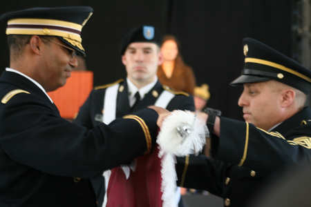Left to right, Army Col. Van Coots, commander of the Walter Reed Health Care System; Army Spc. Sascha Jung; and Army Command Sgt. Maj. Rudy DelValle, the health care system's top enlisted soldier, carefully furl the Walter Reed Health Care System flag at a July 27, 2011, ceremony, casing the unit's colors for transition to the new Walter Reed National Military Medical Center in Bethesda, Md. DOD photo by Terri Moon Cronk