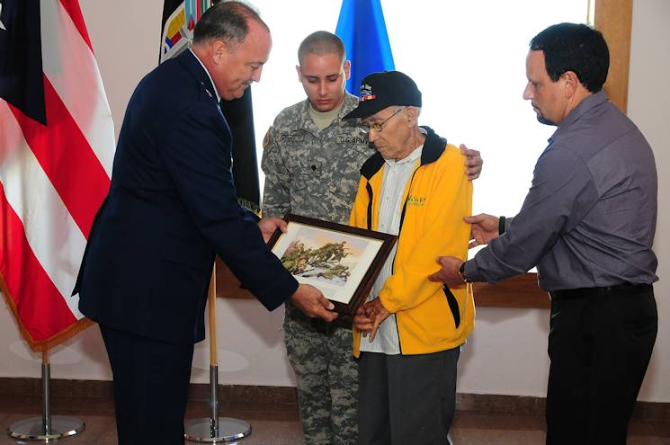 The Adjutant General of Puerto Rico, Armed Forces Brig. Gen. Juan J. Medina Lamela, gives a special gift to Julio Burgos Santiago, veteran of the 65th Infantry Regiment during the ceremony to present a captured Nazi flag to the Puerto Rican National Guard in San Juan on December 19, 2013. Observing the moment are Sec. Wesley Ortiz, member of A Company 1 Battalion 65th Infantry Regiment and grandson of Mr. Santiago and retired Col. Arnaldo Claudio. More than 65,000 Puerto Ricans participated in all Armed Forces branches during World War II. (Courtesy Photo)