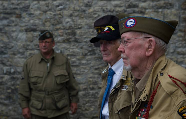 "James ""Pee Wee"" Martin, at center, and Donald R. Burgett attend a memorial ceremony for Joseph ""Jumpin' Joe"" Beyrle, June 5, 2014, in Saint-Côme-Du-Mont, France. Martin and Burgett served in the same unit as Beyrle on D-Day, June 6, 1944, and honored their fellow 506th Parachute Infantry Regiment, 101st Airborne Division comrade, on the 70th anniversary of the liberation of Normandy. (Photo by USAF Senior Airman Alex Riedel)"