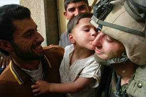 Little Iraqi boy giving a young U.S. troop a kiss