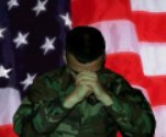 soldier praying with flag in background