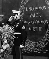 "Marine at attention in salute while standing in front of ""Uncommon Valor"" memorial."